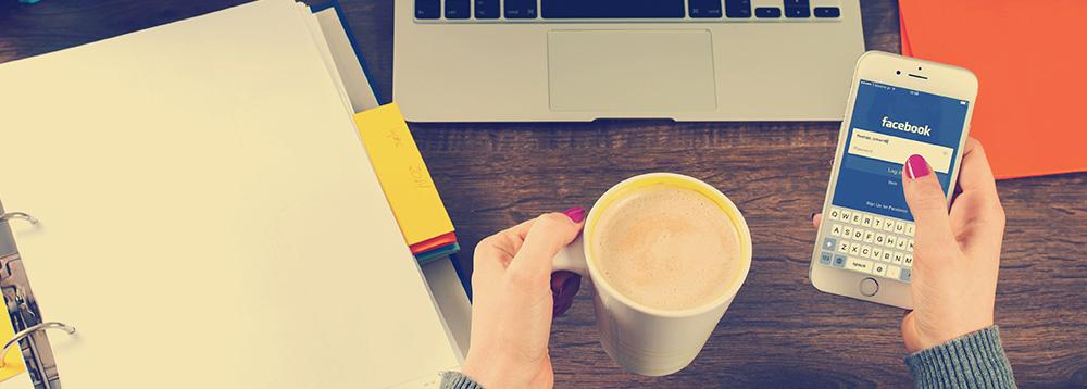 como-conquistar-fieis-na-internet-mulher-acessando-facebook-pelo-smartphone-tomando-cafe