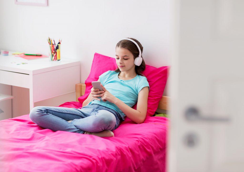 streaming para radio criança em cima da cama com fone de ouvido