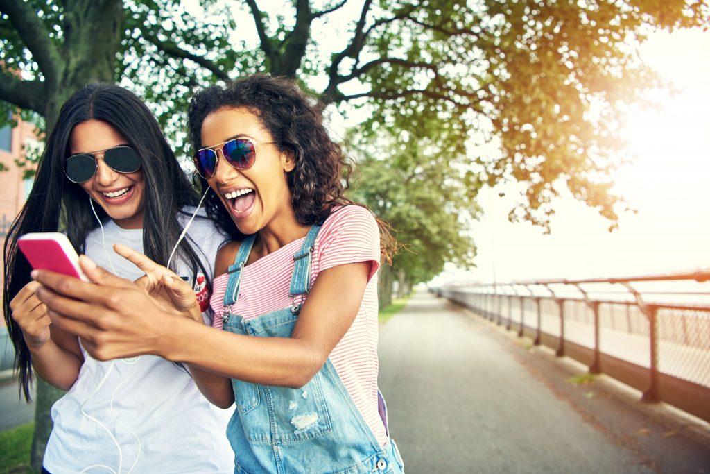 o-que-e-streaming-duas-mulheres-na-praca-assistindo-video-no-celular