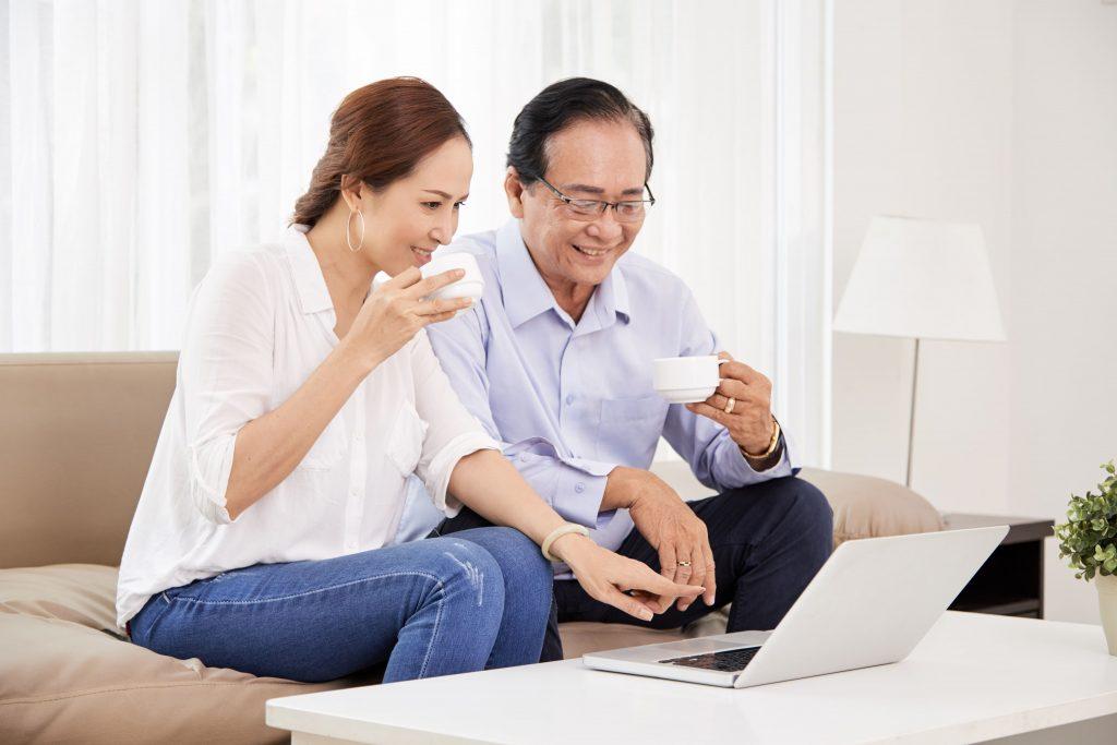 homem e mulher de branco assistindo pelo computador