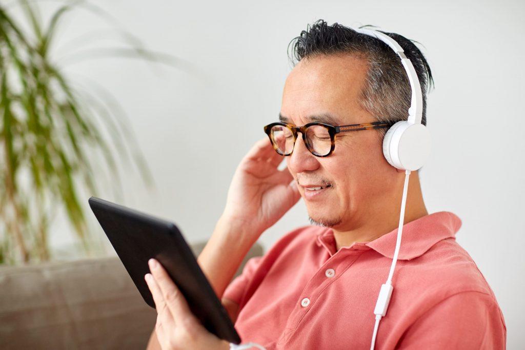 avanco-da-tecnologia-homem-oriental-escutando-pelo-tablet-fone-de-ouvido