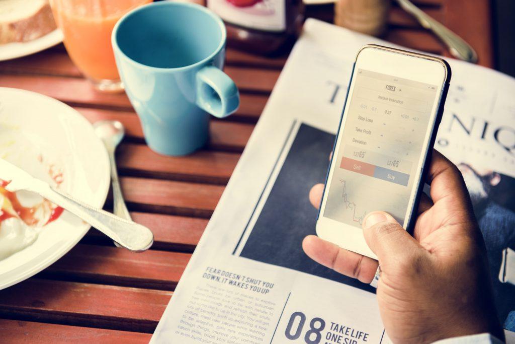 homem-celular-jornal-impresso-noticias-mesa-lanche