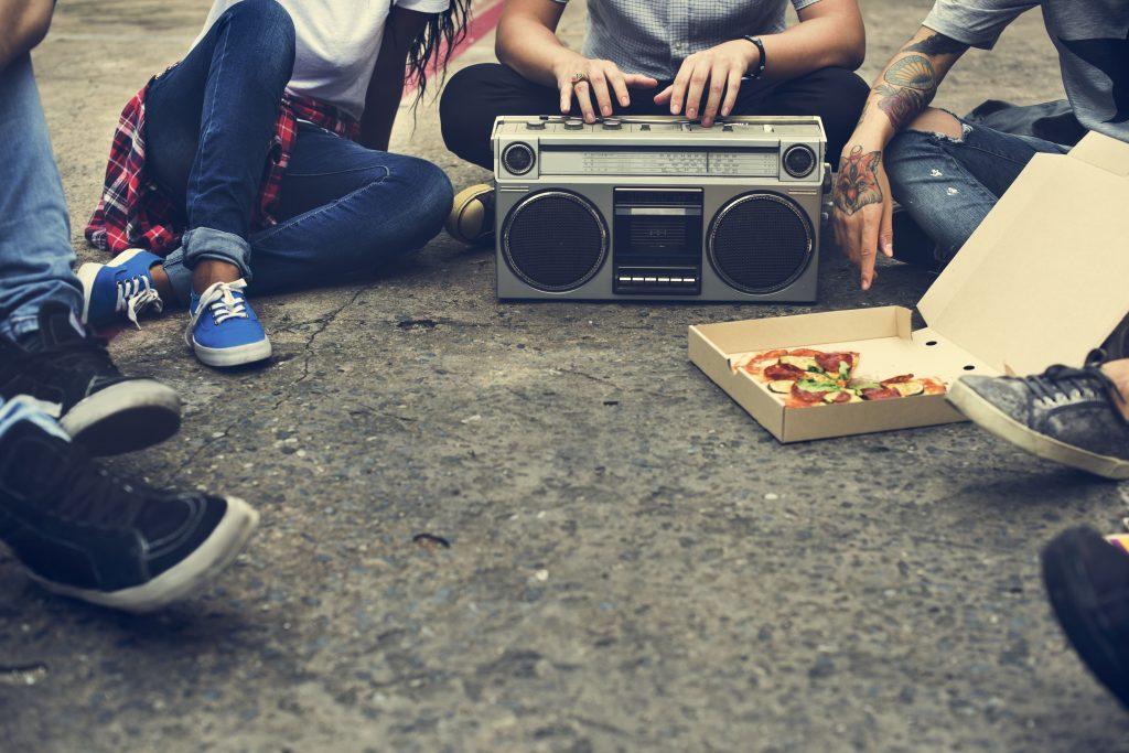 radio-online-jovens-sentados-no-chao-rodeados-por-um-pedaco-de-pizza-e-um-aparelho-de-radio