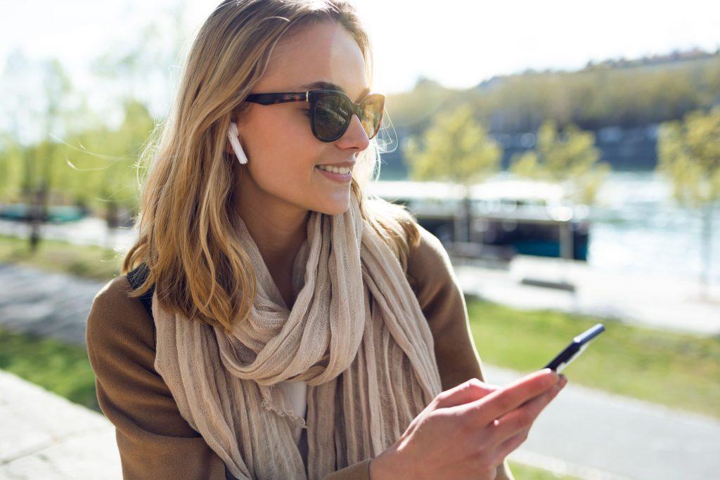 radio-online-mulher-ao-ar-livre-escutando-no-fone-de-ouvido-e-mexendo-no-celular