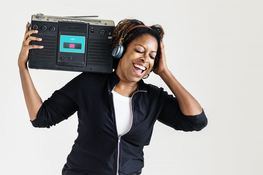 radio-online-mulher-negra-escutando-com-um-aparelho-de-radio-nos-ombros