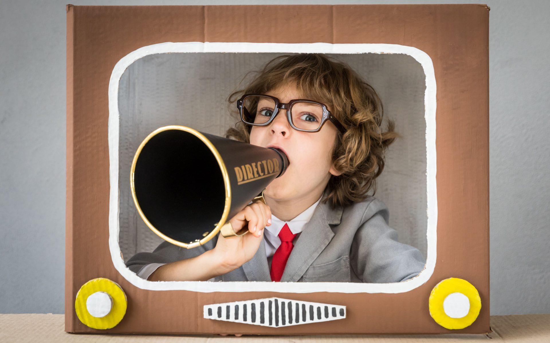 marketing-promocional-crianca-terno-e-gravata-anunciando-na-televisao-com-megafone