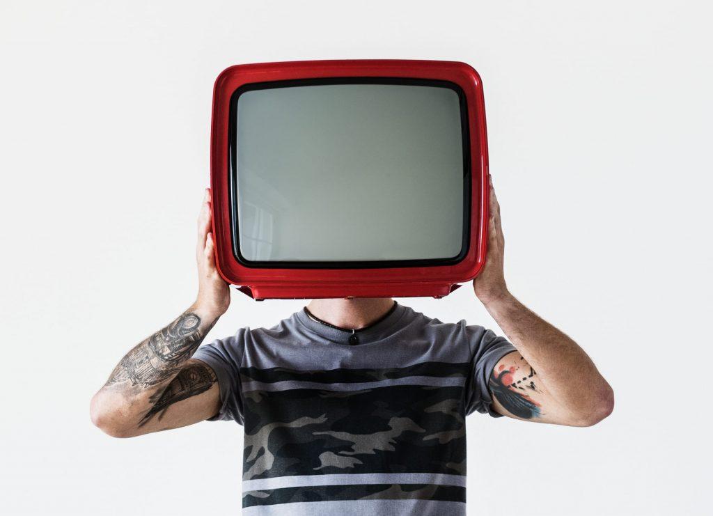 tv-e-internet-homem-com-tatuagem-segurando-televisao-vermelha
