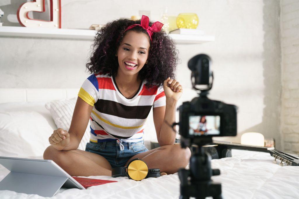 tv-e-internet-mulher-jovem-cabelos-cacheados-gravando-video-no-quarto