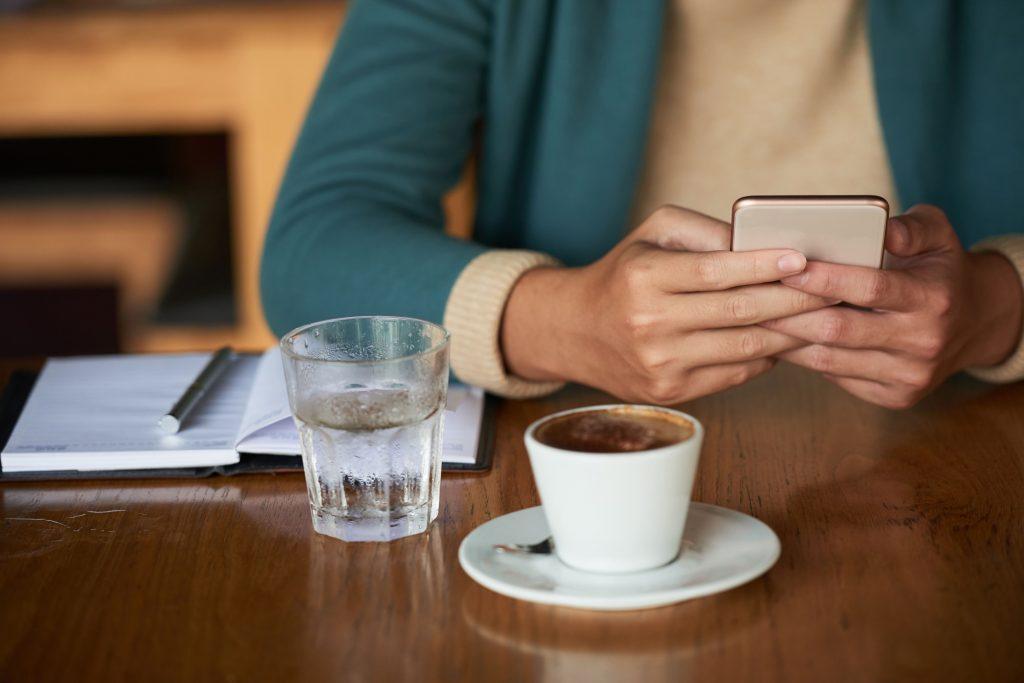 mulher-tomando-café-anotando-na-agenda-e-mexendo-no-celular