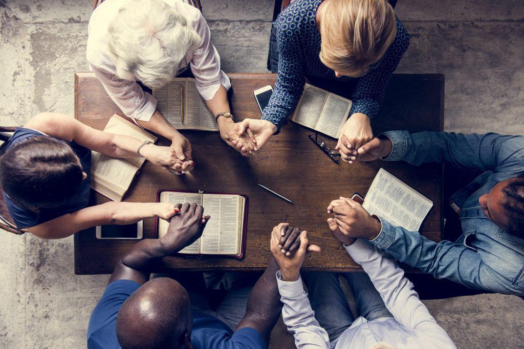 comunicacao-e-evangelizacao-pessoas-dando-as-maos-rezando-intercessao-biblia