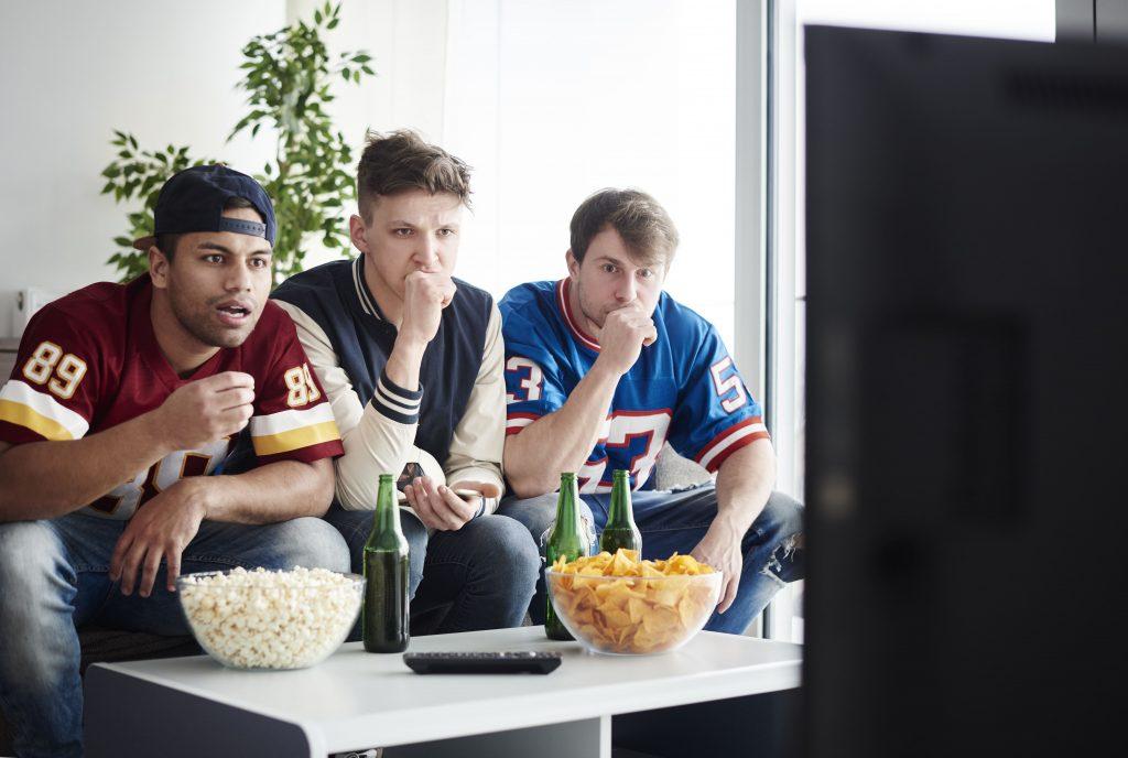 novas-tecnologias-tres-rapazes-assistindo-televisao-apreensivos-esporte