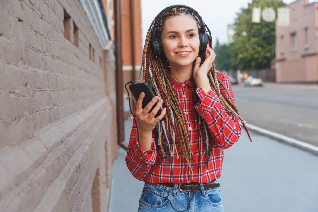 garota-na-rua-escutando-com-fone-de-ouvido-pelo-celular