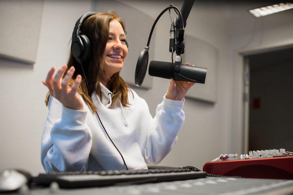 locutora-feliz-estudio-fone-de-ouvido-mesa-de-operacao