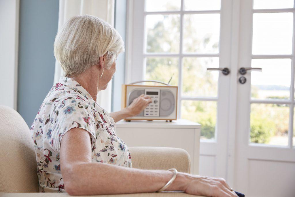 tudo-sobre-o-radio-senhora-sentada-no-sofa-sintonizando-aparelho-de-radio